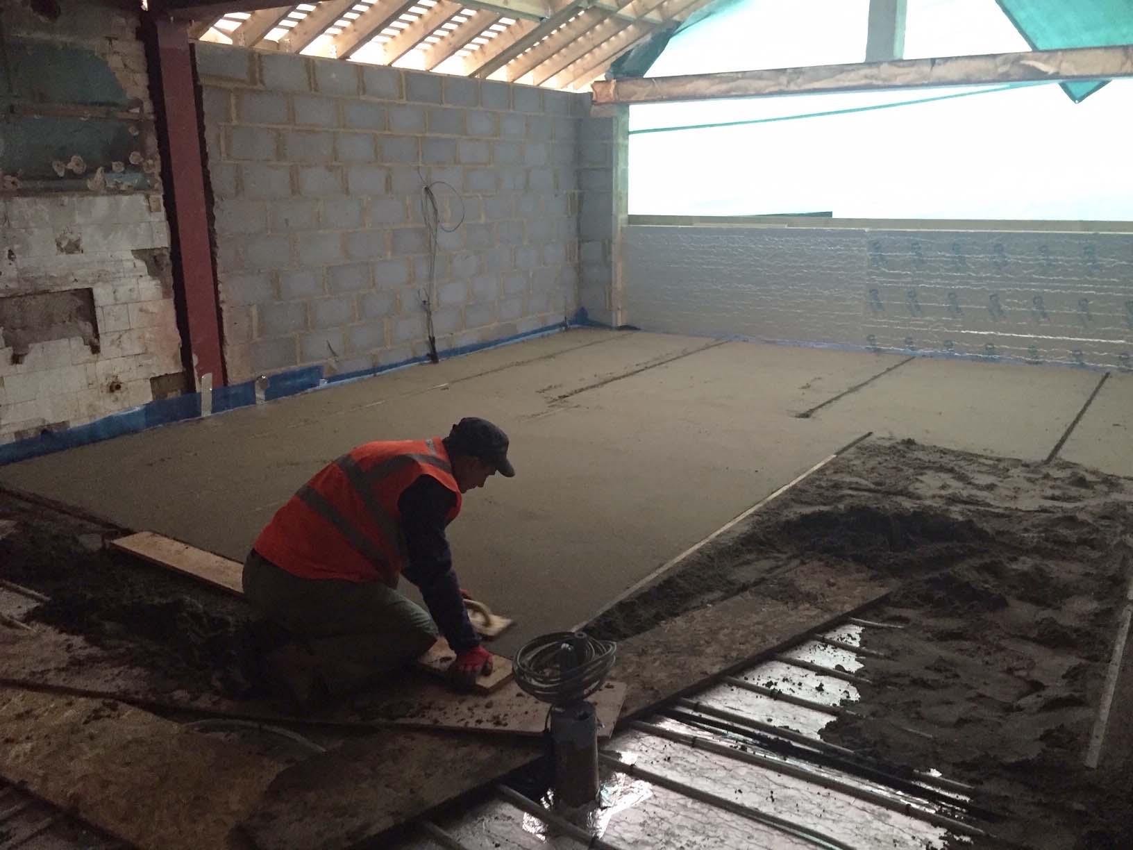 floor screed being levelled by a builder, house floor screeder